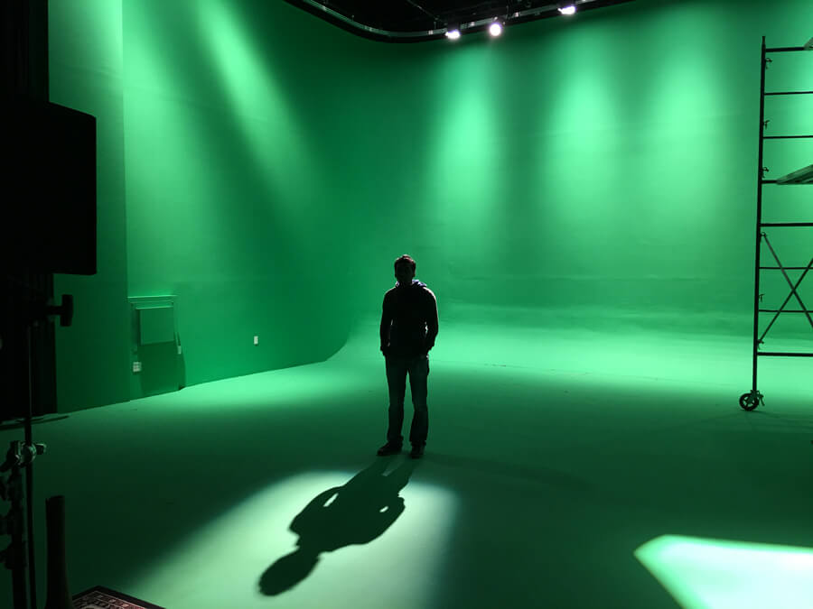 Man and his shadow in front of green screen