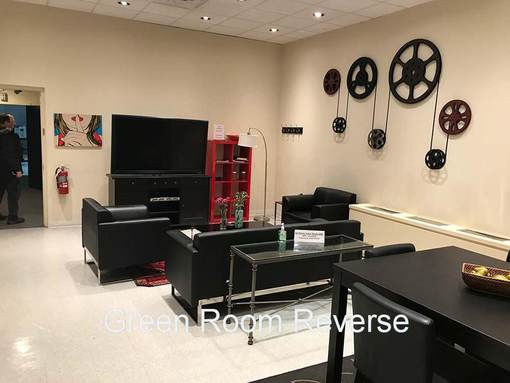 Chelsea Central Green Room Reverse with black couches tables and large monitor