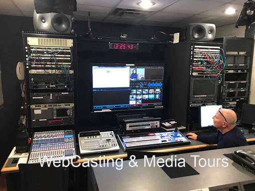 """Control Room with TriCaster 8000 and audio mixing board and large 55"""" monitor and man with bald head in chair"""