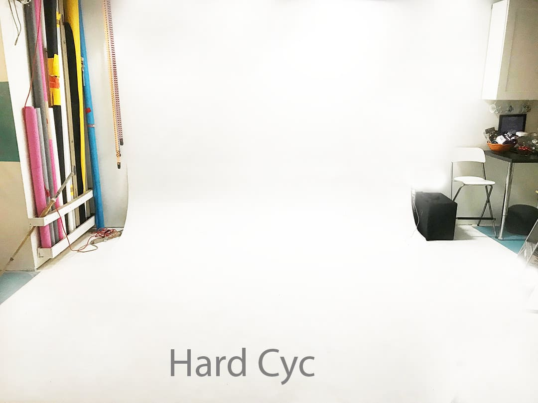 Hard White Cyc in studio with colored rolls of seamless paper on the left