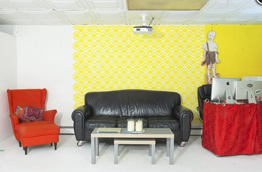 Tribeca Video Studio Loft with yellow wall, black couch and red chairs