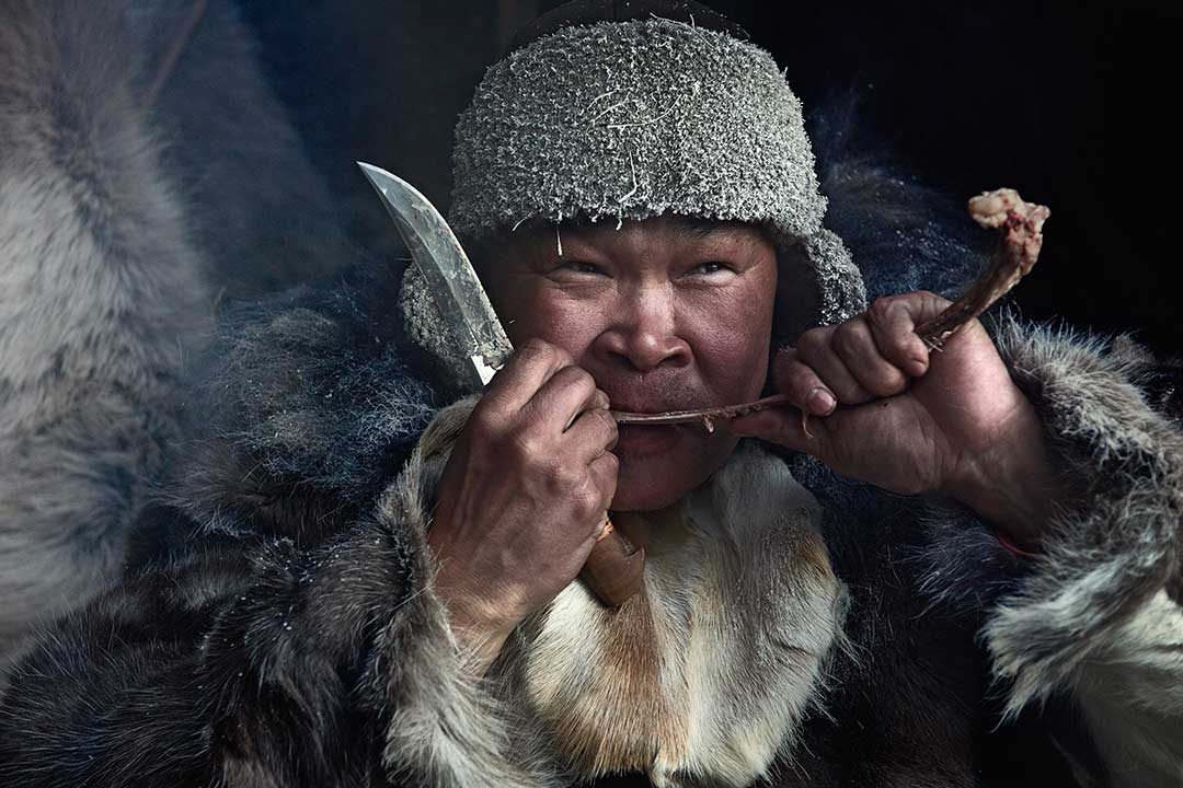 Smiling Mongolian Man in Yurt eating meat with a long knife