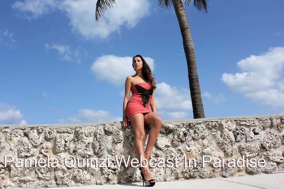 Pamela Quinzi WebCast in Paradise. Beautiful woman in red bathing suit with palm tree
