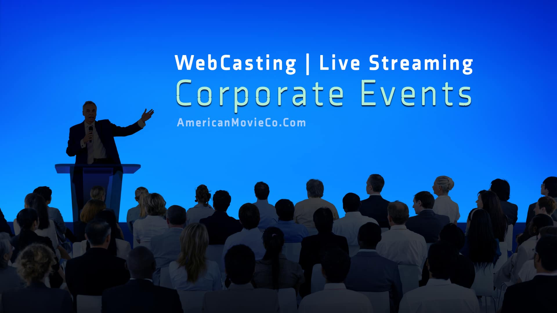 WebCasting Large group at Corporate Event  listen to man at podium - all in silhouette - blue background.