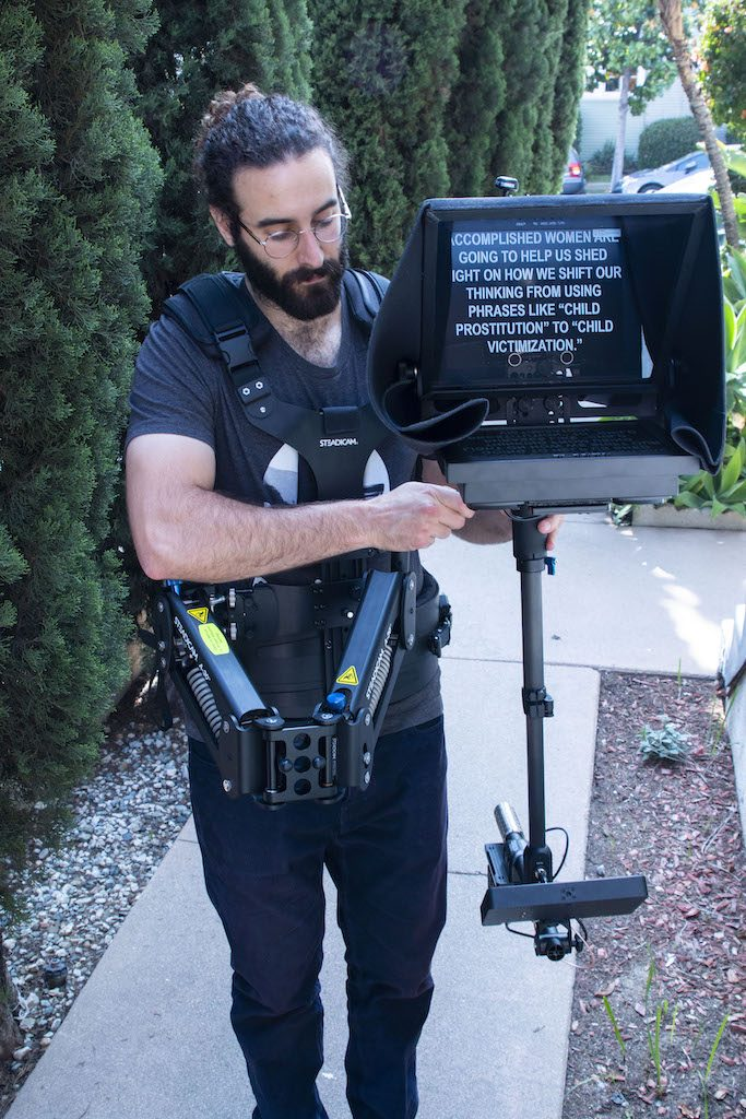 SteadiCam Prompter with Operator, bearded man dressed in black holding the unit - outside