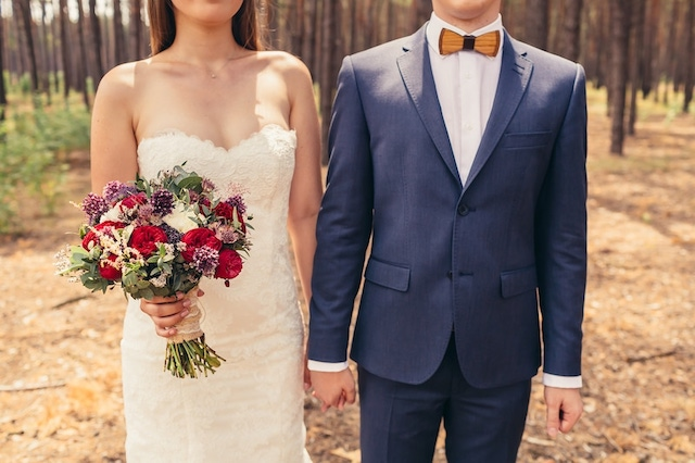 Wedding WebCast: Cropped picture of bride holding bouquet and holding hands with groom in a forest background.