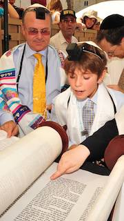 WebCast Young boy pointing to Scroll - adults looking on.  Bar Mitzvah.